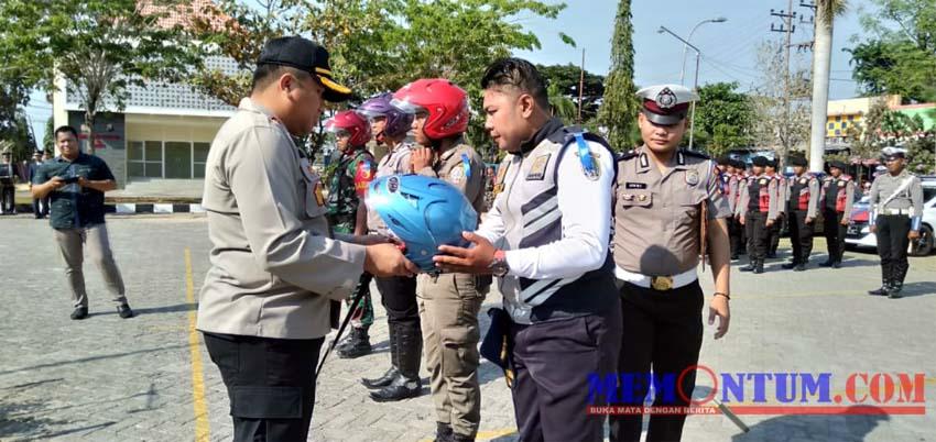 Kapolres Sampang AKBP Didit BWS saat menyerahkan helm kepada anggota Polres, TNI, Satpol PP dan Dinas Perhubungan Sampang. (zyn)