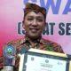 Bupati Sampang H Slamet Junaidi saat menunjukkan sertifikat dan trofi Swasti Saba Wiwerda. (Humas Pemkab Sampang)