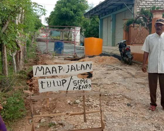 Akses jalan ditutup sementara oleh warga akibat perbaikan rabat beton di Dusun Panjelin, Desa Sekobanah Daya, Sampang, Jawa Timur